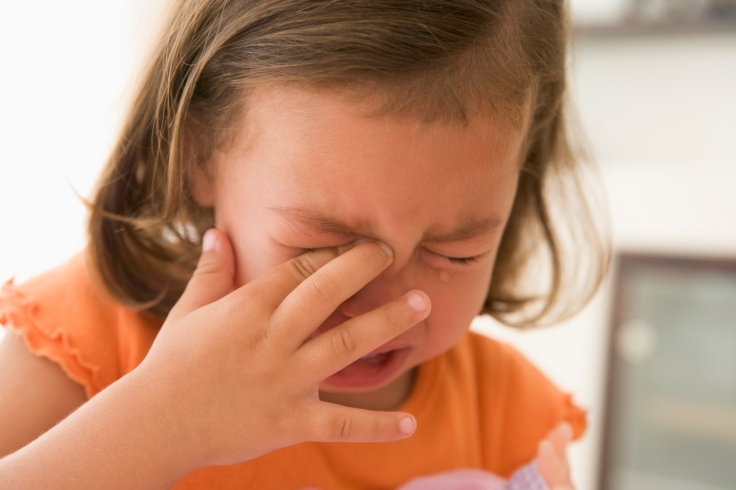 Young girl indoors crying